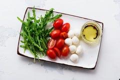 Моццарелла, томаты вишни и arugula, который служат в белых керамических прямоугольных плитах с оливковым маслом над серой предпос стоковые фотографии rf