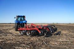 Мощный трактор вспахивая поле Стоковая Фотография