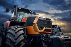 Мощный трактор на предпосылке захода солнца Стоковая Фотография
