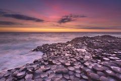 Мощёная дорожка гиганта в Северной Ирландии на заходе солнца Стоковые Изображения