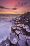 Мощёная дорожка гиганта в Северной Ирландии на заходе солнца Стоковое Фото