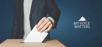 Моя концепция дел голоса Избиратель человека держит руку голосование над урной для избирательных бюллетеней стоковые изображения rf