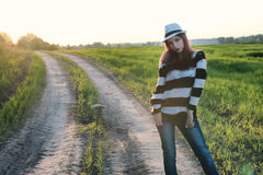Мода девушки в поле на заходе солнца Стоковые Изображения