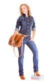 Мода джинсовой ткани. Полнометражная девушка студента в голубых джинсах кладет книги в мешки Стоковые Фотографии RF