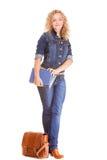 Мода джинсовой ткани. Полнометражная девушка студента в голубых джинсах кладет книги в мешки Стоковая Фотография RF