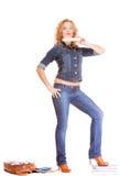 Мода джинсовой ткани. Полнометражная девушка студента в голубых джинсах кладет книги в мешки Стоковое Изображение