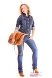 Мода джинсовой ткани. Полнометражная девушка студента в голубых джинсах кладет книги в мешки Стоковая Фотография