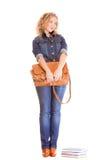 Мода джинсовой ткани. Полнометражная девушка студента в голубых джинсах кладет книги в мешки Стоковое Изображение RF