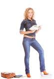 Мода джинсовой ткани. Полнометражная девушка студента в голубых джинсах кладет книги в мешки Стоковые Фото