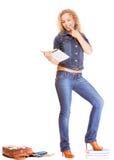 Мода джинсовой ткани. Полнометражная девушка студента в голубых джинсах кладет книги в мешки Стоковое фото RF