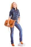Мода джинсовой ткани Полнометражная девушка студента в голубых джинсах кладет книги в мешки Стоковые Фотографии RF