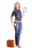 Мода джинсовой ткани Полнометражная девушка студента в голубых джинсах кладет книги в мешки Стоковое Изображение