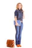 Мода джинсовой ткани Полнометражная девушка студента в голубых джинсах кладет книги в мешки Стоковое Изображение RF