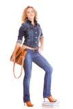 Мода джинсовой ткани Полнометражная девушка студента в голубых джинсах кладет книги в мешки Стоковые Изображения