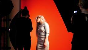 Мода кулуарная: белокурая модель девушки играет длинные волосы - фотограф фотографирует в студии акции видеоматериалы