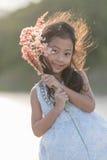 мода ребенк Одежды милой маленькой азиатской девушки нося белые и трава цветка в ее руке Стоковые Изображения