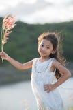 мода ребенк Одежды милой маленькой азиатской девушки нося белые и трава цветка в ее руке Стоковая Фотография