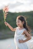 мода ребенк Одежды милой маленькой азиатской девушки нося белые и трава цветка в ее руке Стоковая Фотография RF