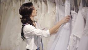 Мода свадьбы менеджера салона выбирает белое платье для невесты сток-видео