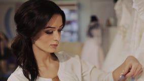 Мода свадьбы менеджера салона выбирает белое платье для невесты видеоматериал