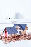 Модели небольших домов среди монеток Стоковое Изображение