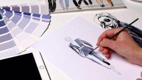 Модельер получает краску щетки на эскизе платья конец вверх сток-видео