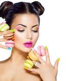 Модельная девушка принимая красочные macaroons Стоковые Фотографии RF