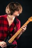 Модельная красная рубашка фланели играя электрическую гитару Стоковое фото RF