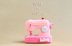 Модельная розовая швейная машина с шрифтом делает для того чтобы приказать Стоковые Фото