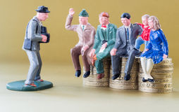 Модельная семья сидит на монетках английского фунта Стоковая Фотография RF