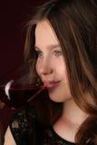 Модельное выпивая вино конец вверх темнота предпосылки - красный цвет Стоковые Фото