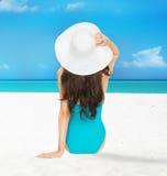 Модельное усаживание в купальнике с шляпой Стоковое Изображение RF