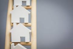 Модельные дома на рангах деревянной лестницы свойства Стоковые Фотографии RF