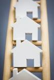 Модельные дома на рангах деревянной лестницы свойства Стоковая Фотография