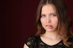 Модельные укусы ее губа конец вверх темнота предпосылки - красный цвет Стоковое Фото