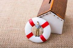 Модельный дом и спасательный жилет с человеком вычисляют Стоковая Фотография