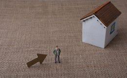 Модельный дом и стрелка около человека вычисляют Стоковая Фотография RF