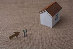 Модельный дом и стрелка около человека вычисляют Стоковое Фото
