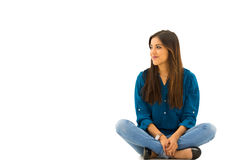 Модель брюнет нося сидеть вскользь одежд удобный на белой предпосылке усмехаясь к камере Стоковое Изображение