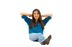 Модель брюнет нося сидеть вскользь одежд удобный на белой предпосылке усмехаясь к камере Стоковая Фотография RF