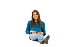 Модель брюнет нося сидеть вскользь одежд удобный на белой предпосылке усмехаясь к камере Стоковое фото RF