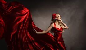 Модель в красном платье, женщине очарования представляя ткань шелка летания Стоковые Фотографии RF
