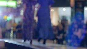 Модель в платье идет на подиум, выставку дефила моды, модель в высоких пятках на выставке платья на подиуме в светлых лампах, акции видеоматериалы