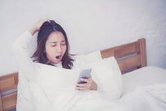 модель женщины азиатская держа мобильный телефон с бодрствованием вверх в спальне Стоковые Фото