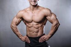 Модель красивого фитнеса мужская представляя в студии на белой задней части серого цвета Стоковое Изображение