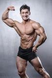 Модель красивого фитнеса мужская представляя в студии на белой задней части серого цвета Стоковое фото RF