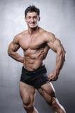 Модель красивого фитнеса мужская представляя в студии на белой задней части серого цвета Стоковые Фото