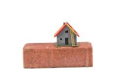 Модель красного кирпича и небольшого дома изолированная на белизне Стоковые Изображения