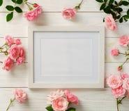 Модель-макет рамки плаката, взгляд сверху, розовые розы на белой деревянной предпосылке Принципиальная схема праздника Плоское по Стоковое фото RF