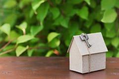 Модель дома картона с ключом против зеленого цвета выходит предпосылка Приобретение, рента и концепция недвижимости страны констр стоковые изображения